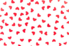 Valentine`s day decorative soft blur abstract pattern of red hearts confetti on white background. royalty free stock image