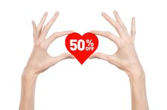 Valentine's Day discounts topic: Hand holding a card in the form of a red heart with a discount of 50% on an isolated Stock Image