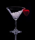 Valentine's day drink. A Martini glass with ice and heart on black background Stock Images