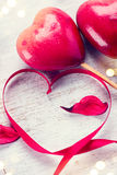 Valentine`s Day. Elegant red satin gift ribbon and couple of red hearts stock photo