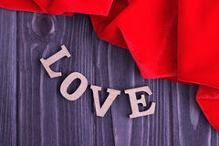 Valentine`s day elegant still life with love lettering and red fabric on wooden background. Valentine`s day elegant background with love lettering and red fabric Royalty Free Stock Photography