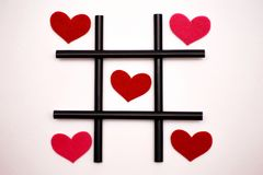 Valentine`s Day, February 14, tic-tac-toe concept, on a white background, black tubules for juice and red felt hearts. Valentine`s Day, February 14, tic-tac-toe royalty free stock photo