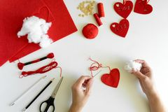 Valentine`s day felt crafts. Woman hands sewing red hearts. DIY. Flat lay. Top view stock photos
