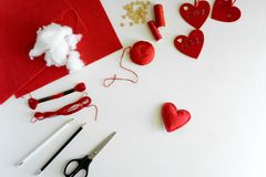 Valentine`s day felt crafts. Woman hands sewing red hearts. DIY. Flat lay. Top view.  royalty free stock photography
