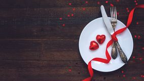 Valentine's Day Festive table setting, flat lay with two red heart shape chocolate candies on white plate, fork, knife and red. Ribbons on wooden table royalty free stock photo