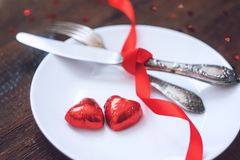Valentine's Day Festive table setting, mockup with two red heart shape chocolate candies on white plate, fork, knife and red. Ribbons on wooden table. Valentine royalty free stock photos