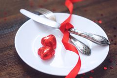 Valentine's Day Festive table setting, mockup with two red heart shape chocolate candies on white plate, fork, knife and red. Ribbons on wooden table. Valentine stock photo