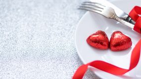 Valentine's Day Festive table setting with two red heart shape chocolate candies on white plate, fork, knife and red ribbons on. Silver glitter background stock image