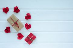 Red paper hearts with gift boxes, on white wooden background, Va. Valentine`s Day, gift boxes and red paper hearts, with space to write. Cenital plane Stock Photos