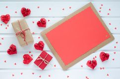 Red paper hearts with gift boxes, on white wooden background, Va. Valentine`s Day, gift boxes and red paper hearts, with space to write. Cenital plane Royalty Free Stock Photos