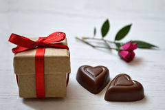 Valentine's Day gift, chocolate hearts and a rose. On light background royalty free stock photography