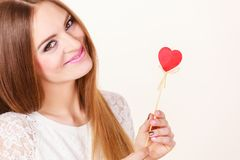 Beautiful woman holding heart shaped hand stick Stock Photo