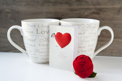 Valentine's day gift with greeting card and two cups. Valentine's day gift box with greeting card and two cups on wooden background. Close-up Royalty Free Stock Photos