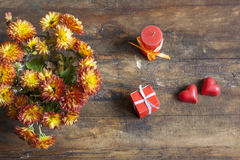 Valentine's Day gift, red chocolate hearts, candle and golden chrysanthemum on wooden background Royalty Free Stock Images