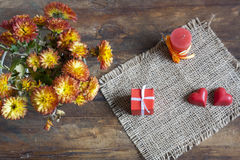 Valentine's Day gift, red chocolate hearts, candle and golden chrysanthemum on wooden background Stock Photos