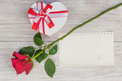 Valentine`s Day gift, rose and paper on wooden background. Stock Images
