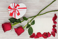 Valentine`s Day gift, roses and paper on wooden background. Royalty Free Stock Photo