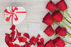 Valentine`s Day gift, roses and paper on wooden background. Royalty Free Stock Photography