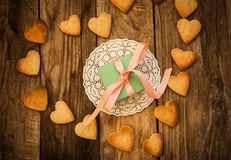 Valentine`s day. Gift on the white napkin and  Cookies in the Shape of Heart at Valentine Day. On the wooden background Royalty Free Stock Photos