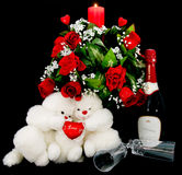 Valentine's day gifts and decorations. Valentine's day setup consisting of a pair of white furry soft toys, red wine, wine glasses, red roses, and a red candle Stock Photos