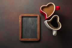 Valentine`s Day with gifts, a heart-shaped box, cups of coffee, heart-shaped cookies and a blackboard. Top view with copy space stock photos