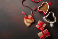 Valentine`s Day with gifts, a heart-shaped box, cups of coffee, heart-shaped cookies, macaroons and a blackboard. Top view with stock photography