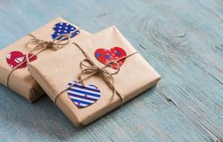 Valentine's day gifts in kraft paper, paper hearts on blue wooden surface. Vintage and rustic style Royalty Free Stock Photos