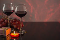 Valentine`s Day with a glass of red wine, grapes, gift, candles. Stock Photo