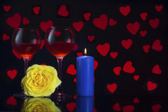 Valentine`s Day with a glass of red wine, yellow rose, blue candle and background with red hearts Royalty Free Stock Photo