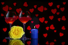Valentine`s Day with a glass of red wine, yellow rose, blue candle and background with red hearts Royalty Free Stock Photos