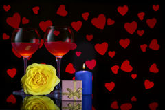 Valentine`s Day with a glass of red wine, yellow rose, blue candle, gift and background with red hearts Royalty Free Stock Images