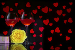 Valentine`s Day with a glass of red wine, yellow rose, blue candle, gift and background with red hearts Stock Image