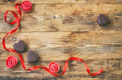Valentine`s Day greeting card, milk chocolate heart shape, rose Royalty Free Stock Images