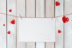 Valentine`s day greeting card on red threads surrounded by hearts on wooden white background royalty free stock photos