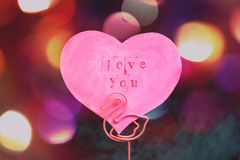 Valentine`s Day greeting card in the shape of a pink heart with an inscription love you in a stand made of pink flamingo royalty free stock photos