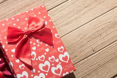 Valentine`s Day greeting card. Top view on romantic composition with gift box copy space on wooden background. Valentine`s Day greeting card. Top view on royalty free stock image
