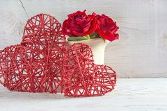 Valentine`s day greeting card: two red wicker heart and bouquet of scarlet roses in jug on rustic white paint wooden background. Two red wicker heart and bouquet stock photos