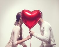 Valentine`s day. Happy joyful couple holding heart shaped air balloon and kissing royalty free stock images
