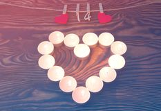 Valentine`s day. Heart of candles. Red wooden hearts with pins and figures of FEB. 14 hanging on the rope on the brown wooden. Background Stock Photo