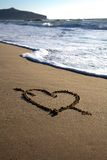 Valentine\'s Day heart with cross and waves. Valentine\'s Day heart with cross on the beach Stock Photos