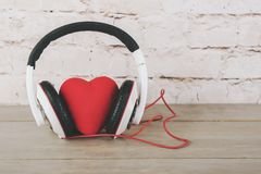 Valentine`s Day. Heart with headphones on a wooden table Royalty Free Stock Photos