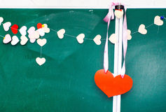 Valentine's day. Heart of paper hanging on blackboard background Royalty Free Stock Images