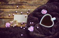 Valentine`s day, heart shaped coffee cup cozy brown scarf. Pink roses, gift box and blank paper tag on an old wooden table Royalty Free Stock Image