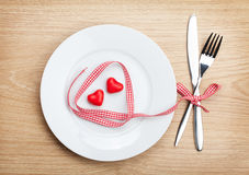 Valentine's Day heart shaped red ribbon over plate with silverwa Stock Image