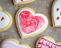 Valentine`s Heart Sugar Cookies with Royal Icing Marble Design. Valentine`s Day heart shaped sugar cookie with artsy marble design in red and white on stone Royalty Free Stock Image