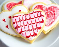 Artsy Valentine`s Heart Sugar Cookies with Royal Icing. Valentine`s Day heart shaped sugar cookies with artsy designs in red and pink on a white plate Stock Photo