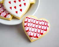 Valentine`s Heart Sugar Cookies with Royal Icing Designs. Valentine`s Day heart shaped sugar cookies with artsy designs in red and pink on a white plate with one Stock Images