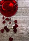 Valentine`s Day heart and wine background. Red Valentine candy hearts at base of wine glass with red wine on gray wood board background stock images