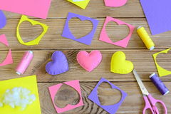 Valentine`s day hearts crafts. Colorful hearts gifts made of felt, felt scraps, scissors, thread on wooden table. Valentine`s day craft project. Valentine`s day Stock Image