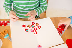 Valentine's Day Hearts: Kids Arts and Crafts. Childs, kids, engaged in a Valentine's Day arts and crafts activity royalty free stock images